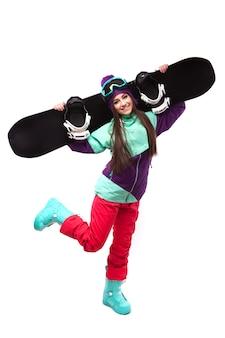 De jonge vrouw in purpere skiuitrusting houdt snowboard op sholders