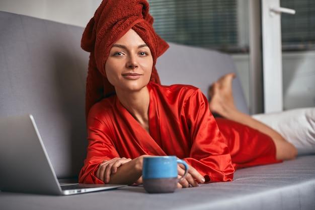 De jonge vrouw in rode badjas en rode handdoek op haar hoofd bevindt zich in keuken dichtbij lijst, drinkt koffie en gebruikt laptop. ochtend, meisje na het douchen drinkt thee en werkt op de computer. werkt thuis.
