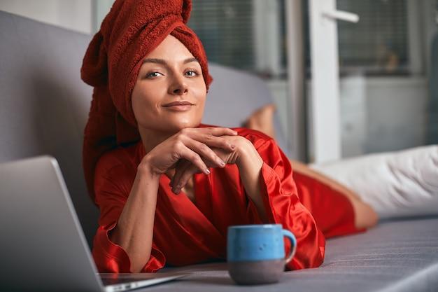 De jonge vrouw in rode badjas en rode handdoek op haar hoofd bevindt zich in keuken dichtbij lijst, drinkt koffie en gebruikt laptop. 's morgens drinkt het meisje na het douchen thee en werkt op de computer.