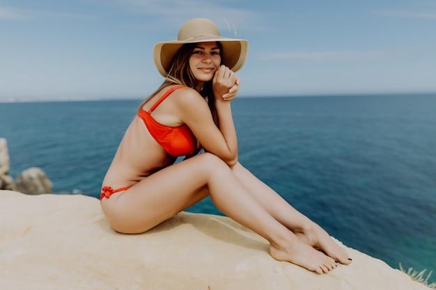 De jonge vrouw in rode bikini en strohoed, zittend op de rand van een heuvel met uitzicht op de oceaan