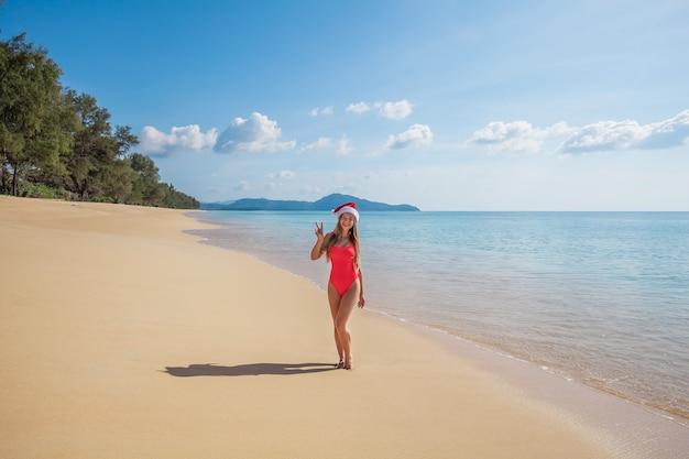De jonge vrouw in rode zwempak en de hoed van de kerstman toont v-tekengebaar op het strand