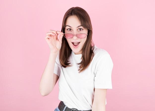 De jonge vrouw in roze bril is zeer verrast als ze naar de camera kijkt en haar bril verlaagt