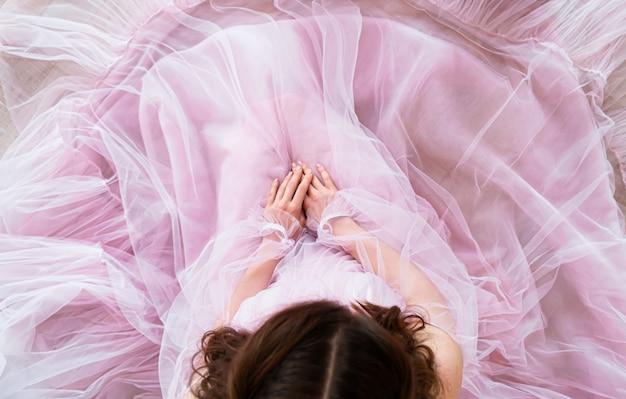 De jonge vrouw in roze elegante kleding stelt voor studiofotoshoot.