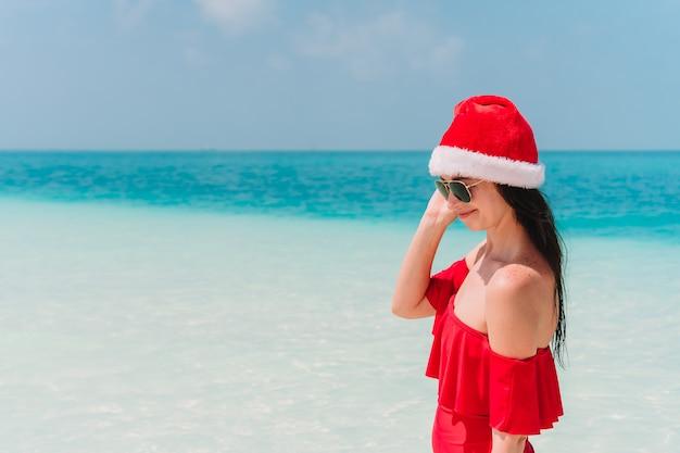 De jonge vrouw in santa hat-het lopen spreidde haar handen op wit zandig strand uit