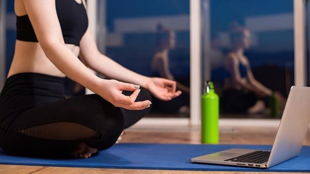 De jonge vrouw in sportkleding mediteert op een yogamat met laptop voor haar