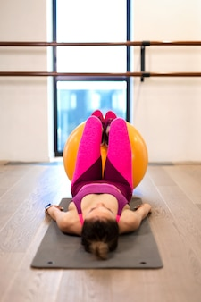 De jonge vrouw in sportwear sportoefening weet gele fitball in gymnastiek. fitness en wellness levensstijl concept