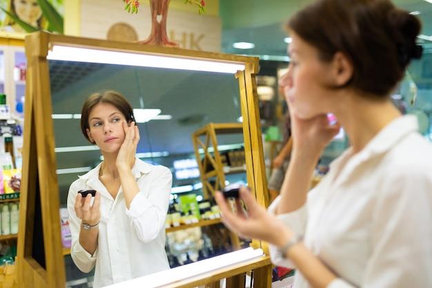 De jonge vrouw in wit overhemd zet op maakt omhoog en bekijkt haar gedachtengang in spiegel