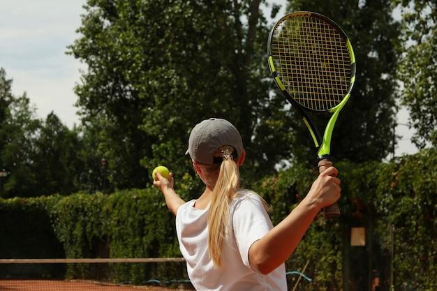 De jonge vrouw in wit t-shirt dient de tennisbal