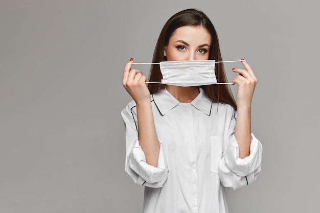 De jonge vrouw in witte medische laag die een medisch beschermend masker toont en het gaat gebruiken, isoleert bij de grijze achtergrond. kopieer ruimte voor uw tekst en product. gezondheidszorg concept