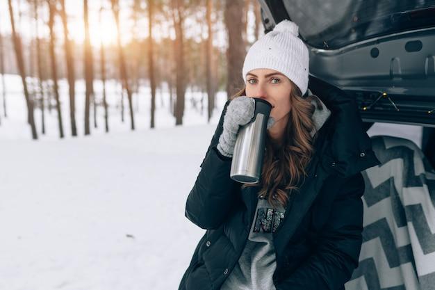 De jonge vrouw in wollen hoed zit in de kofferbak van de auto en houdt een kop hete thee in haar handen