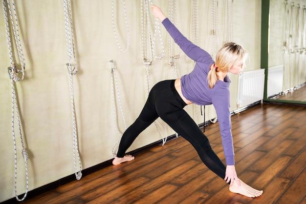 De jonge vrouw in yoga stelt dichtbij muur met kabels