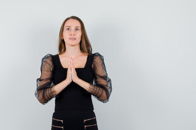 De jonge vrouw in zwarte blouse en zwarte broek die zich in gebed bevindt stelt en ernstig kijkt