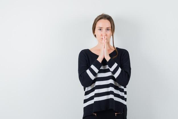 De jonge vrouw in zwarte blouse en zwarte broek die zich in gebed bevindt stelt en gericht kijkt