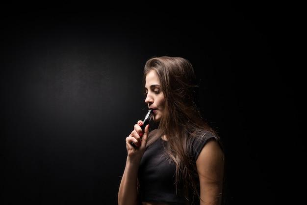 De jonge vrouw in zwarte rookt een elektronische sigaret op donkere muur