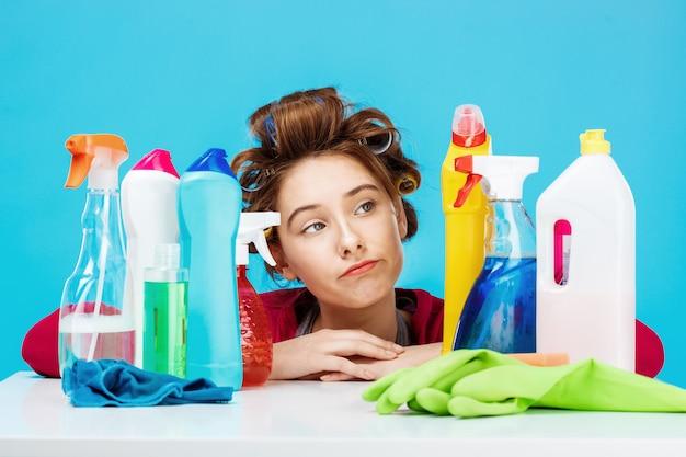 De jonge vrouw kijkt vermoeid zittend achter lijst met schoonmakende hulpmiddelen