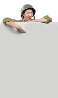 De jonge vrouw kleedde zich in amerikaans ww2 militair eenvormig tonend uithangbord met exemplaarruimte