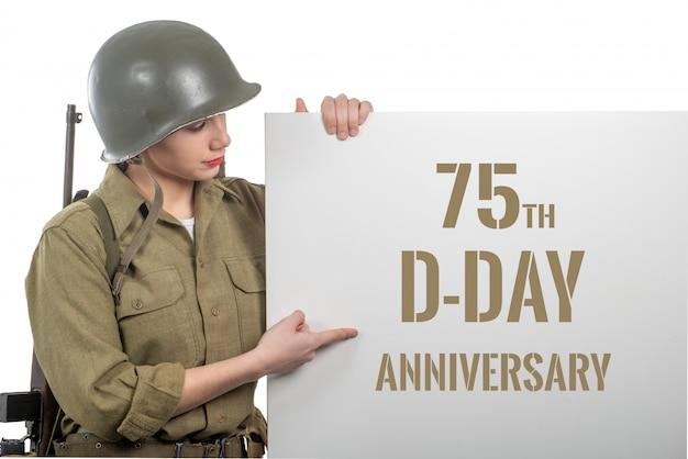 De jonge vrouw kleedde zich in ons wwii militair uniform met helm die uithangbord met d-dagverjaardag toont
