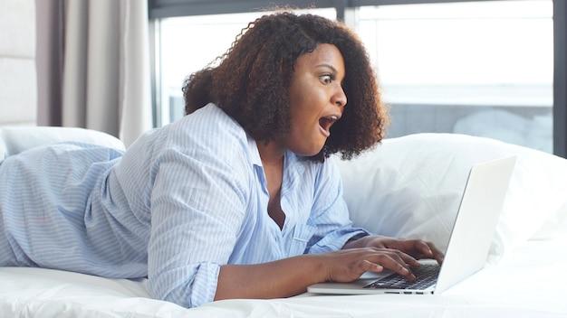 De jonge vrouw kleedde zich in pyjama's die thuis aan laptop werken. afstandswerk. zelfisolatie, quarantaine