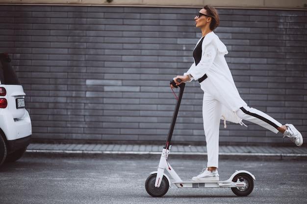 De jonge vrouw kleedde zich in witte berijdende autoped