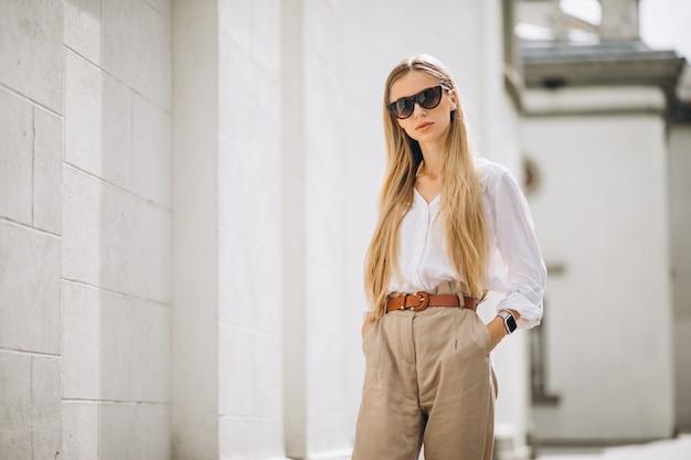 De jonge vrouw kleedde zich uit in de zomeruitrusting in de stad