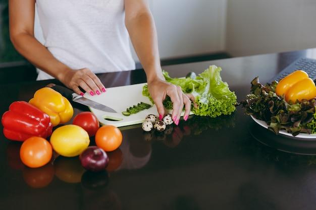 De jonge vrouw kookt in de keuken