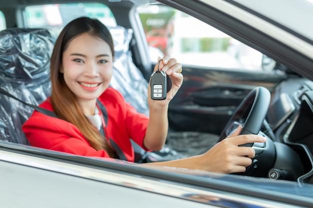 De jonge vrouw koopt een auto met het ontvangen van de sleutels van haar nieuwe auto,