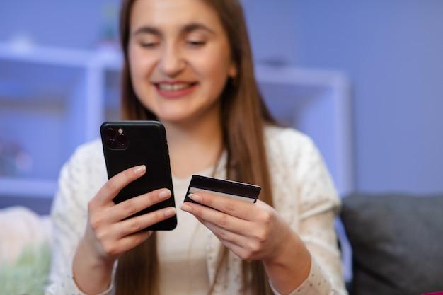 De jonge vrouw koopt online met een creditcard terwijl het zitten op de bank in de woonkamer. vrouw gebruikt smartphone en doet online transacties