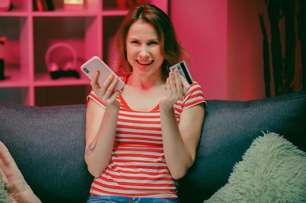De jonge vrouw koopt online met een creditcard terwijl het zitten op de bank in de woonkamer.