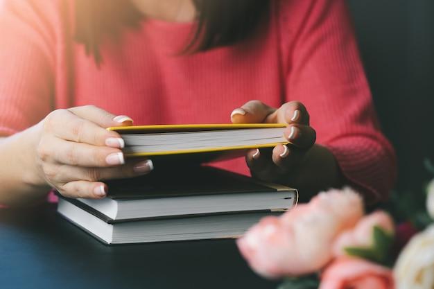 De jonge vrouw leest een boek thuis. onscherpe achtergrond. horizontaal, filmeffect.