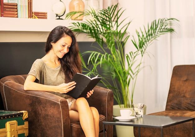 De jonge vrouw leest gelukkig thuis een boek in de bank.