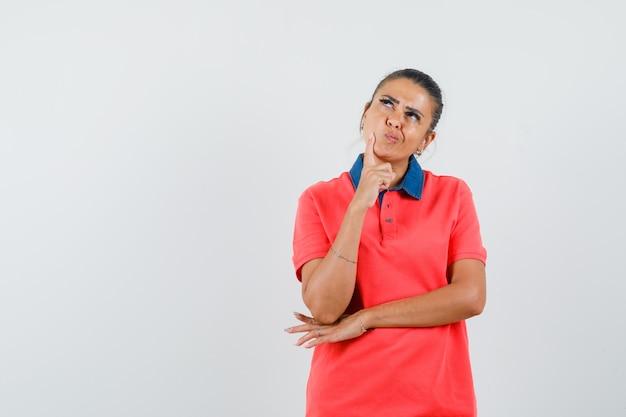 De jonge vrouw leunende wijsvinger op wang, die zich in het denken bevindt stelt in rood t-shirt en peinzend kijkt. vooraanzicht.