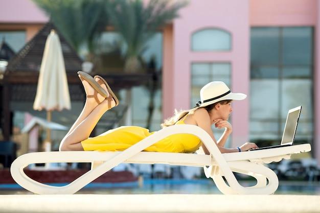 De jonge vrouw ligt op strandstoel werkend aan computerlaptop die met draadloos internet het typen tekst op sleutels in de zomertoevlucht wordt verbonden. zaken doen tijdens het reizen concept.