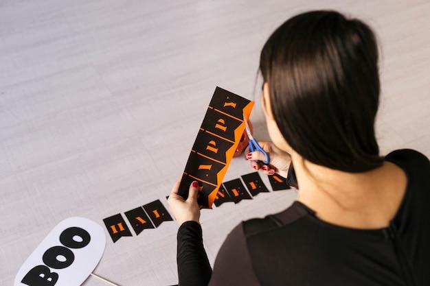 De jonge vrouw maakt halloween-slinger. creatieve diy. home decor project party. halloween ambachten inspiratie.