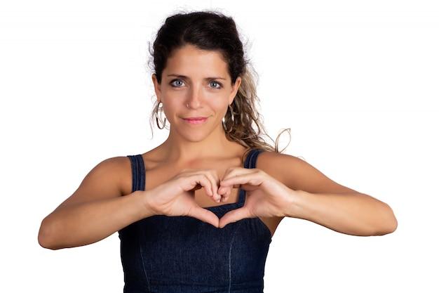 De jonge vrouw maakt hartvorm met handen.