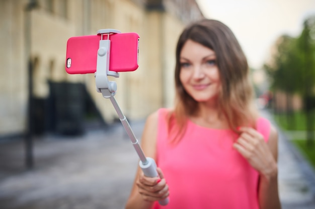 De jonge vrouw maakt selfie met stok voor mobiele telefoon op stadsstraat