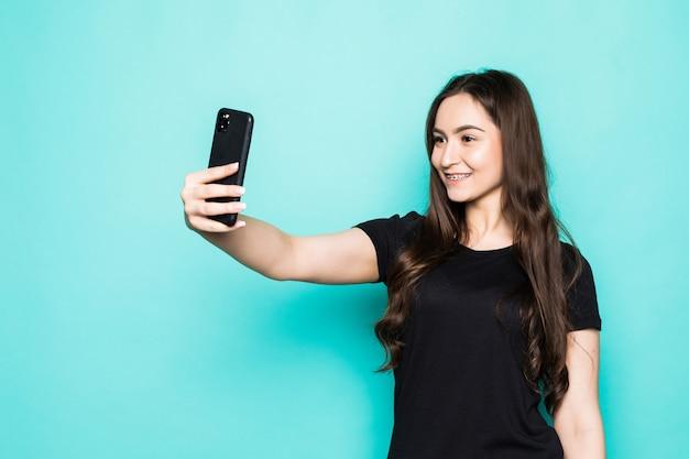 De jonge vrouw maakt selfies nemen die op turkooise muur worden geïsoleerd