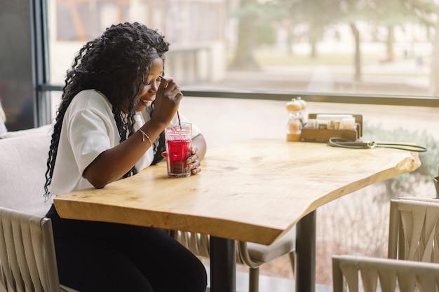 De jonge vrouw met afrohaar drinkt een bessencocktail