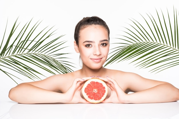 De jonge vrouw met de perfecte citrusvrucht van de huidholding in handen die door palmen worden omringd verlaat geïsoleerd op witte muur