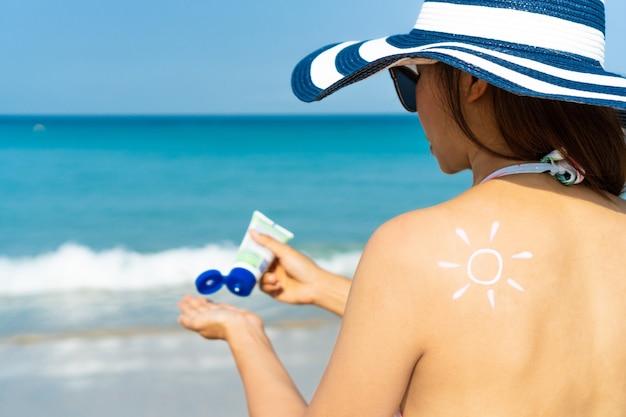 De jonge vrouw met de vorm van de zon op de schouder brengt zonnebrandcrème op haar hand aan. zomer op strand concept.