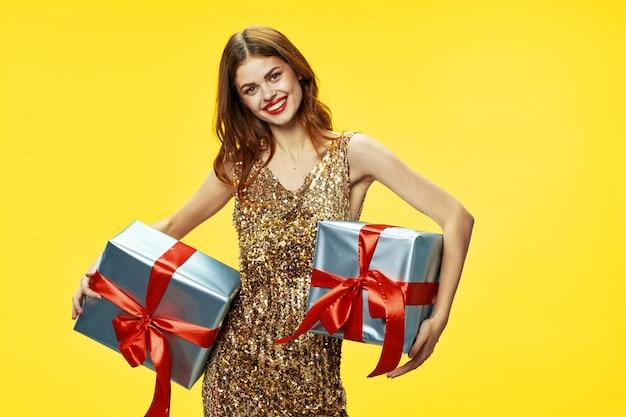 De jonge vrouw met dozen van giften in haar dient de studio op een gekleurde achtergrond in mooie kleren in, verkopende giften, gelukkig kerstmis en nieuwjaar