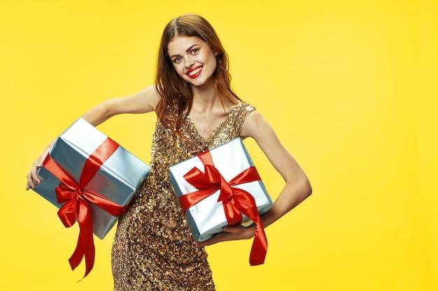 De jonge vrouw met dozen van giften in haar dient mooie kleren in, verkopende giften, gelukkig kerstmis en nieuwjaar