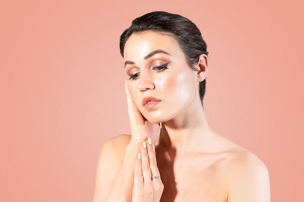 De jonge vrouw met duidelijke huid wat betreft haar overhandigt haar gezicht.