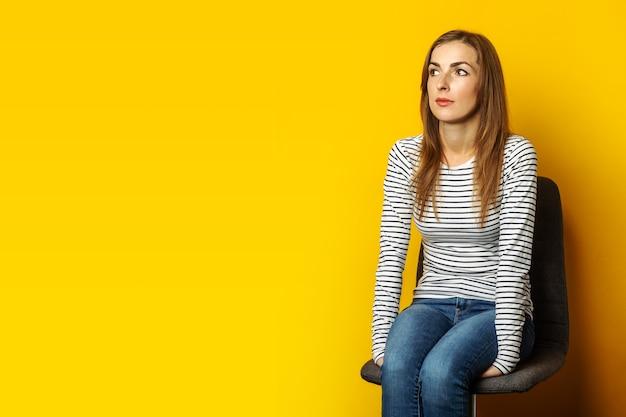 De jonge vrouw met een glimlach zit op een stoel