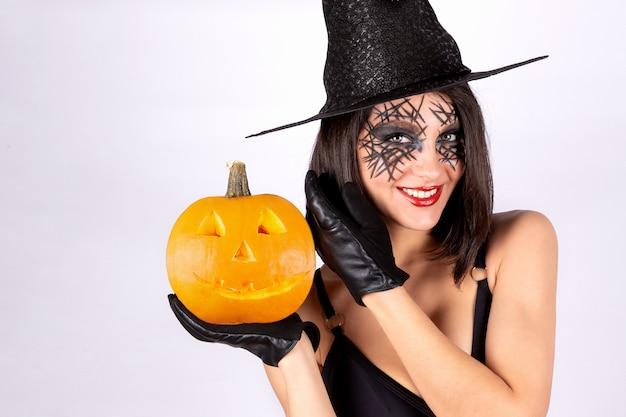 De jonge vrouw met een heksenhoed en enge make-up
