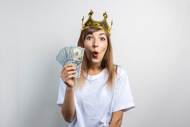 De jonge vrouw met een kroon op haar hoofd en een verbaasd gezicht houdt stapel geld vast.