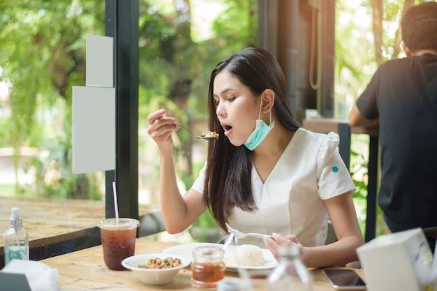 De jonge vrouw met gezichtsmasker heeft voedsel in restaurant, nieuw normaal concept.