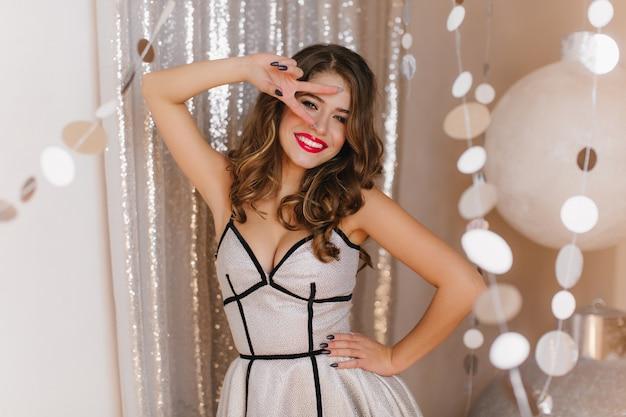 De jonge vrouw met heldere lippen glimlacht en toont vredesteken. dame in stijlvolle zilveren jurk met lederen strepen poseren op glanzende muur.