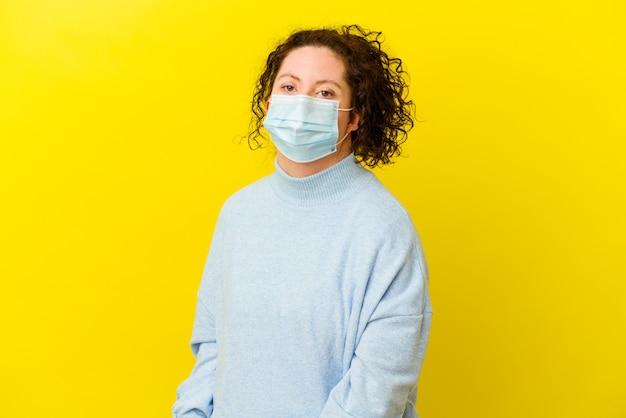 De jonge vrouw met het syndroom van down die een geïsoleerd antivirusmasker draagt, kijkt opzij glimlachend, opgewekt en aangenaam.