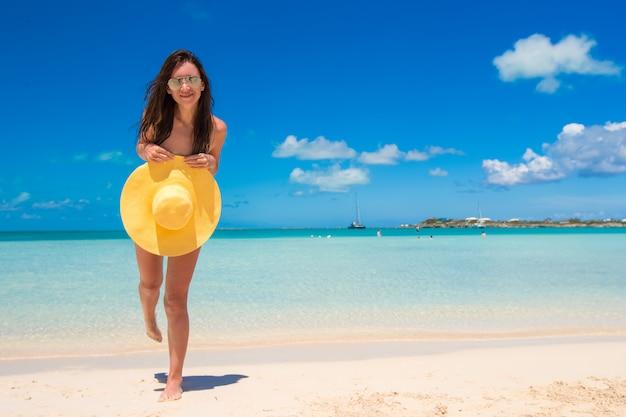 De jonge vrouw met hoed op het strand geniet van caraïbische vakantie