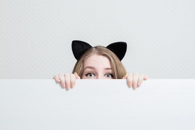 De jonge vrouw met kattenoren op haar hoofd gluurt uit van een witte banner